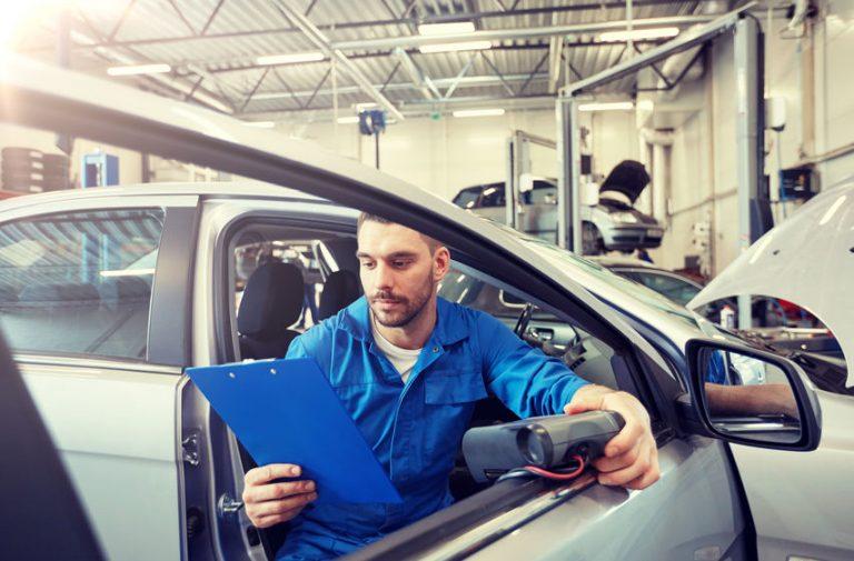 Imagem mostra um homem usando um scanner automotivo.