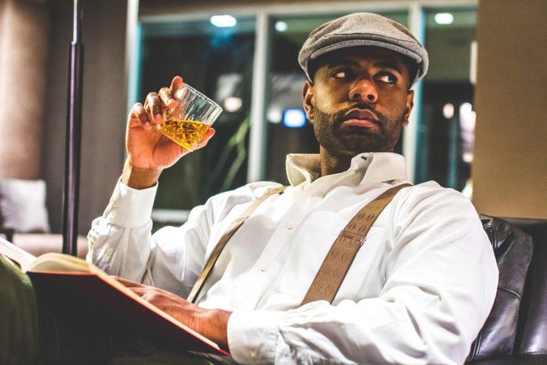 Imagem mostra um homem usando um suspensório sentado e bebendo whisky.