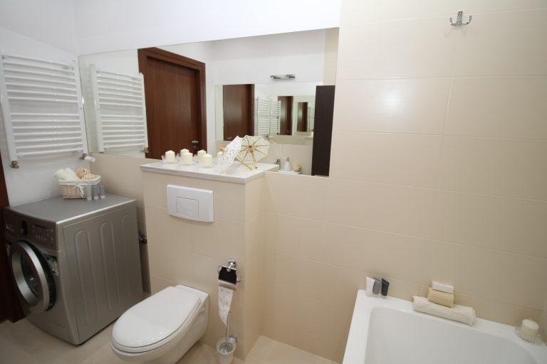 Imagem mostra o banheiro de uma casa, em que o toalheiro térmico está situado sobre a máquina de lavar.
