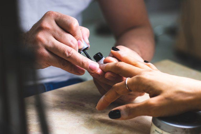 Foto de uma manicure pintando as unhas de uma mulher de preto.
