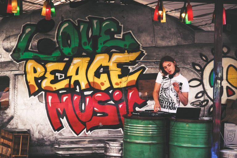 Imagem mostra uma DJ executando sua setlist, bem em frente a uma sucata de uma avião antigo, com a lataria grafitada.