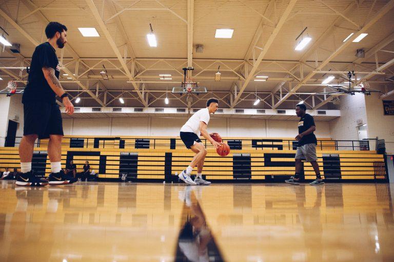 Imagem mostra um jogador treinando em um ginásio, com auxílio de outras duas pessoas. Ele está no centro da quadra, alternando o drible de duas bolas, uma em cada mão.