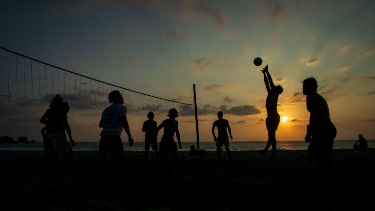 Na foto uma partida de vôlei de praia com diversos jogadores no pôr do sol.