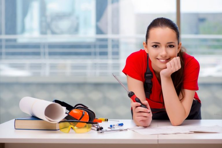 Imagem mostra uma mulher segurando uma chave de fenda apoiada em uma mesa com outras ferramentas.