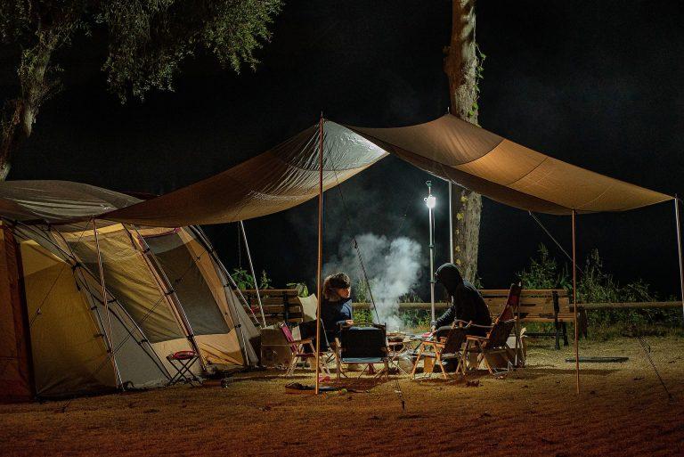Imagem mostra duas pessoas fazendo churrasco em um acampamento.