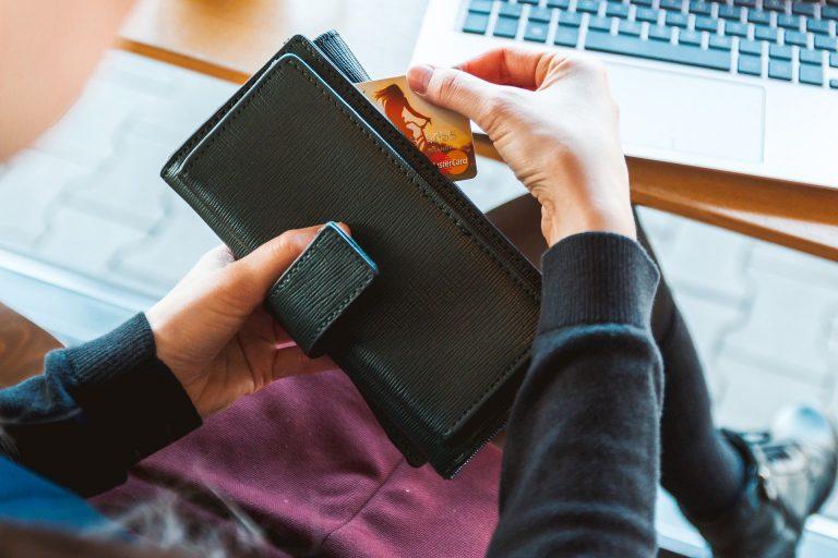 Mulher tirando um cartão de crédito da carteira.