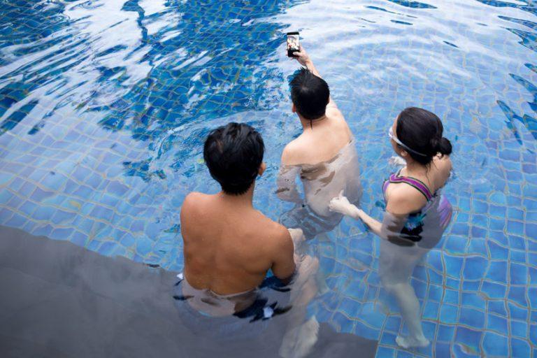 Três pessoas na piscina, tirando selfie com celular.
