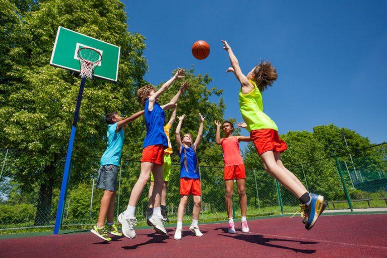 Na foto um grupo de crianças jogando basquete.
