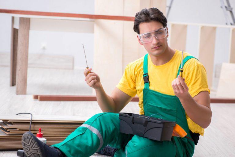 Imagem mostra um homem com uma chave de fenda em uma mão e uma Phillips em outra.