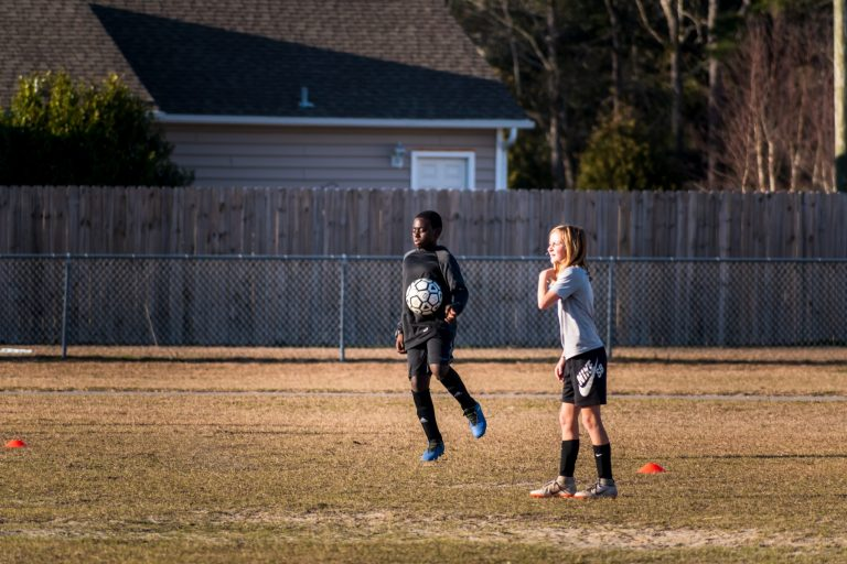 Imagem mostra duas crianças jogando bola num campo com a grama baixa. Uma delas domina a bola no ar, enquanto a outra olha para fora do quadro.