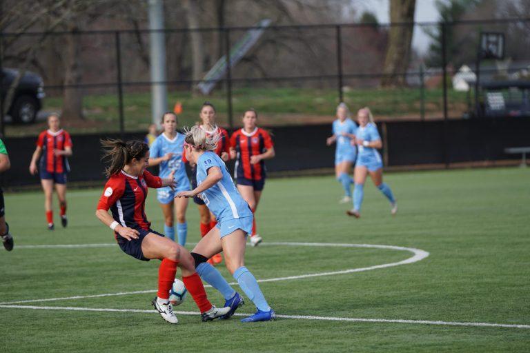 Imagem mostra o momento de um jogo de futebol em que duas jogadoras disputam uma jogada, uma atacando, outra defendendo. A que está defendendo usa chuteiras Mizuno brancas.