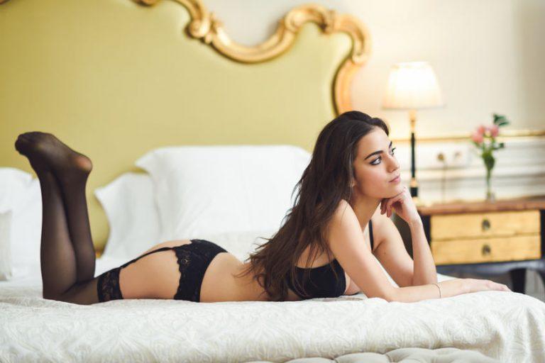 Imagem de mulher deitada usando uma cinta liga preta rendada