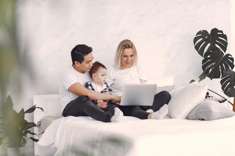 Na foto um casal com um bebê sentado em uma cama junto com um notebook.
