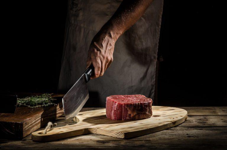 Chef segura cutelo próximo a peça de carne