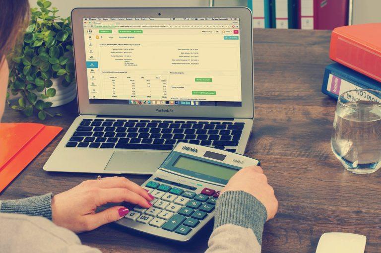 Mulher usando notebook e calculadora.