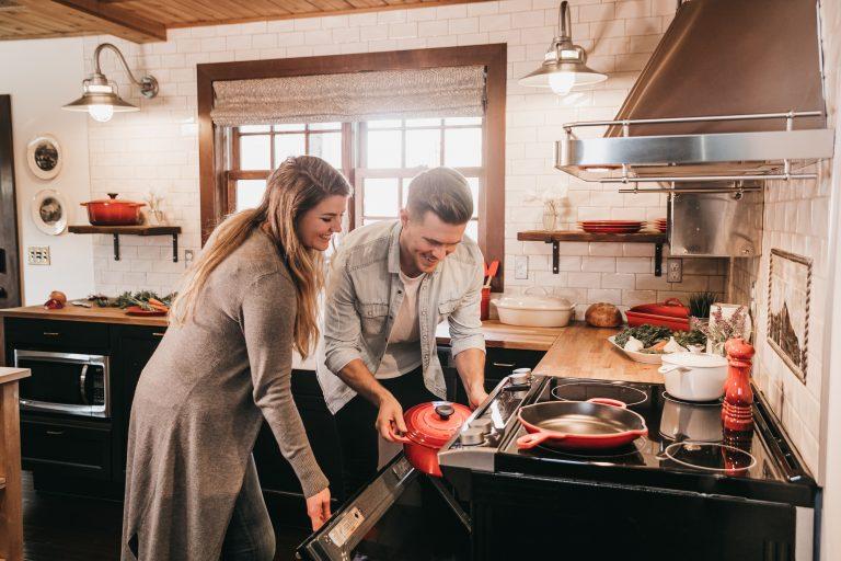 Imagem de casal colocando uma panela de ferro em forno elétrico