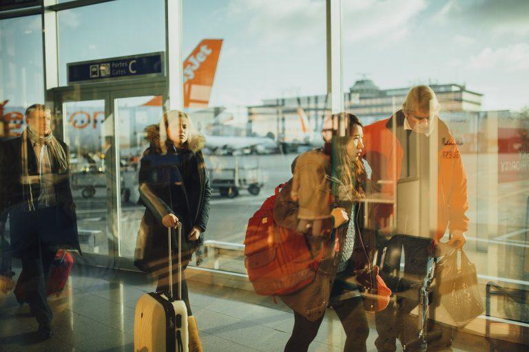 Na foto diversas pessoas em uma fila com um avião atrás.