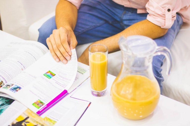Na foto um homem folheando um livro com um copo e uma jarra de suco ao lado.