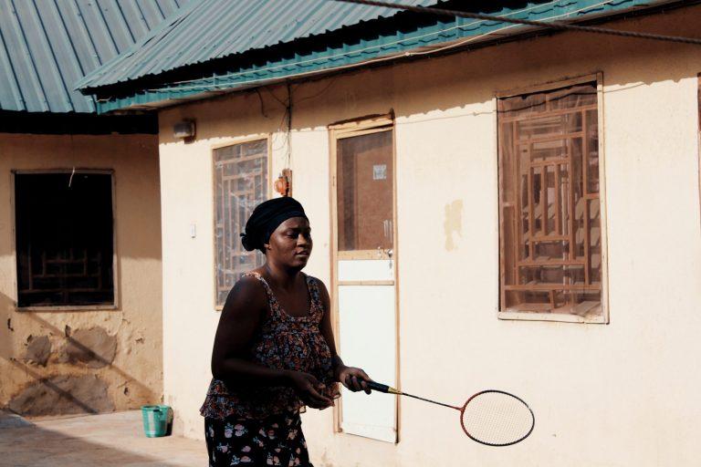 Imagem mostra uma mulher segurando uma raquete de badminton em frente a uma casa.