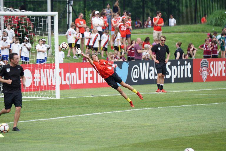 Imagem mostra uma goleira no ar, em meio a uma defesa, durante um aquecimento para um jogo de futebol.