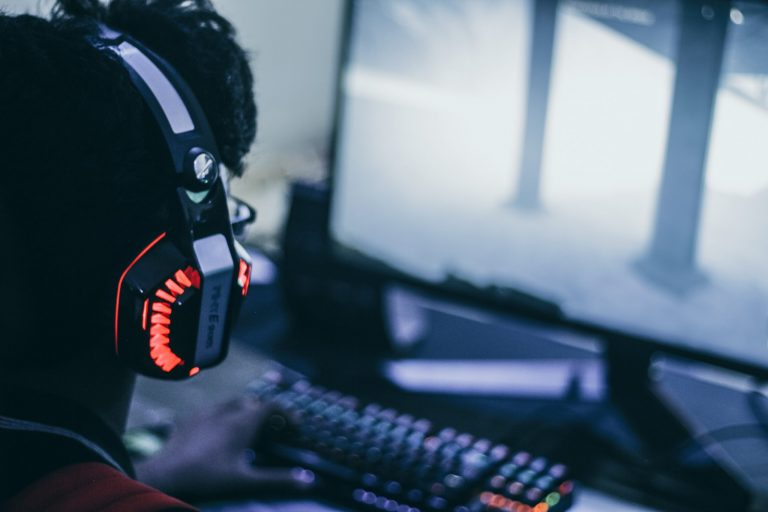 Image of man playing in a gamer setup with a headset