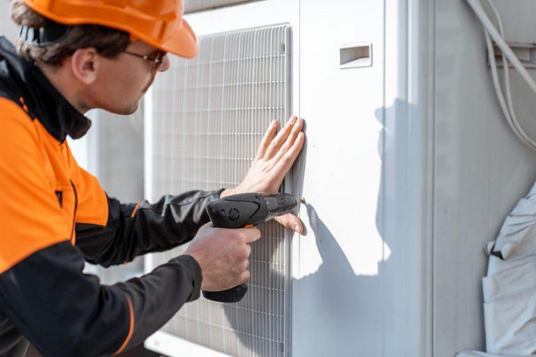 Imagem mostra um homem usando uma parafusadeira em um ar condicionado.