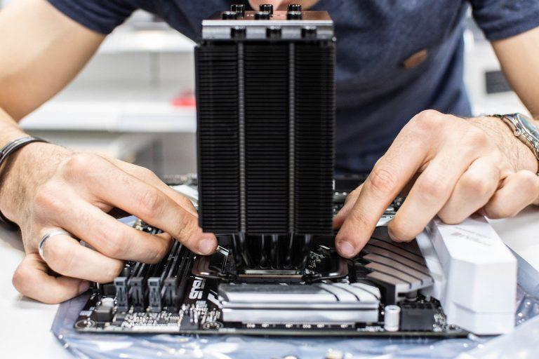 Imagem de pessoa adicionando um hardware na placa mãe
