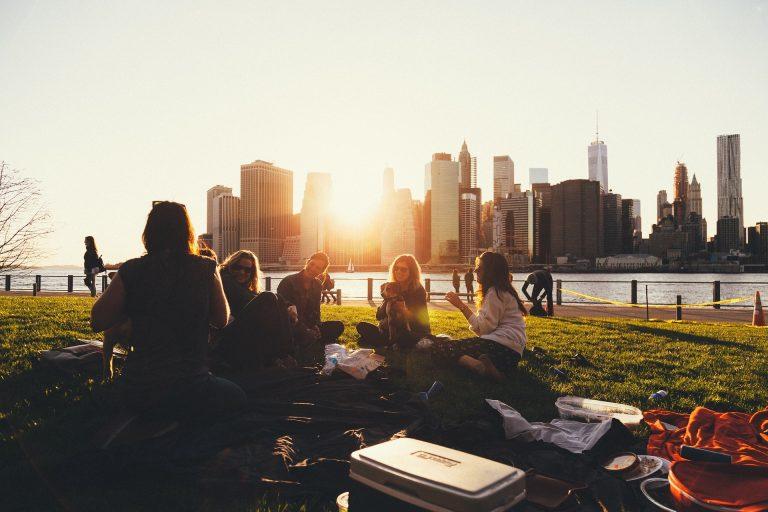 Na foto um grupo de pessoas se divertindo sentadas no gramado de um parque.