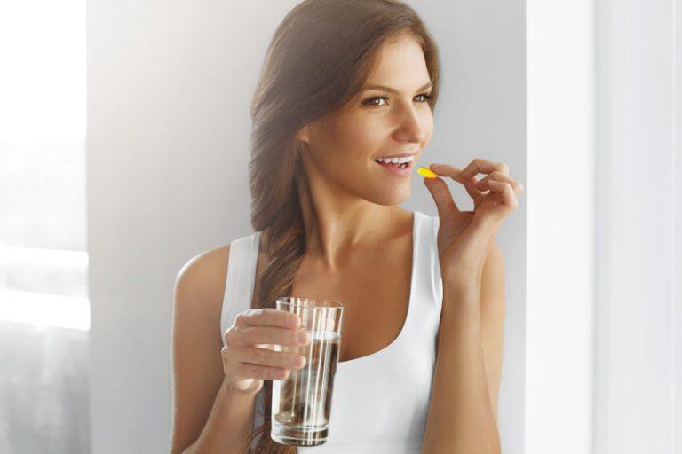 Mulher tomando um comprimido com copo de água.