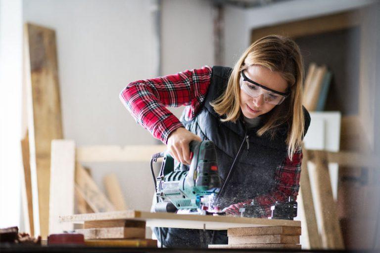 Imagem mostra uma mulher trabalhando com uma serra tico tico.