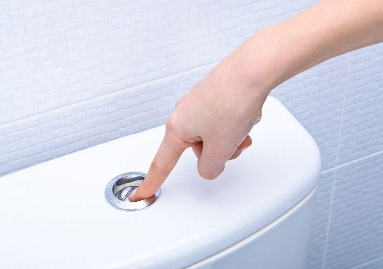 Imagem de pessoa apertando o botão da descarga