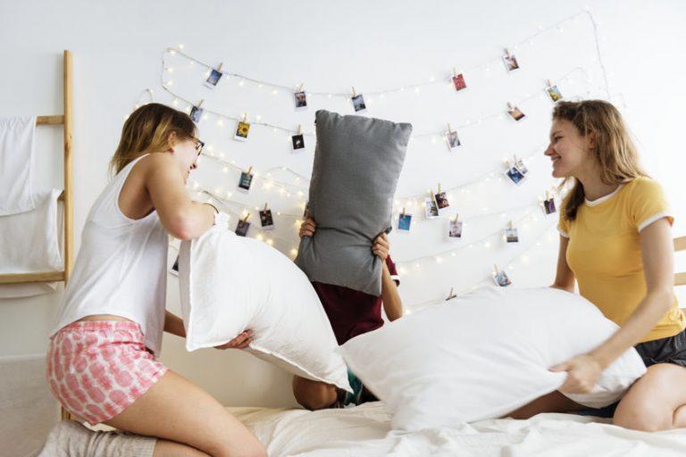 Na foto três mulheres brincando de guerra de travesseiros com um varal de fotos ao fundo.