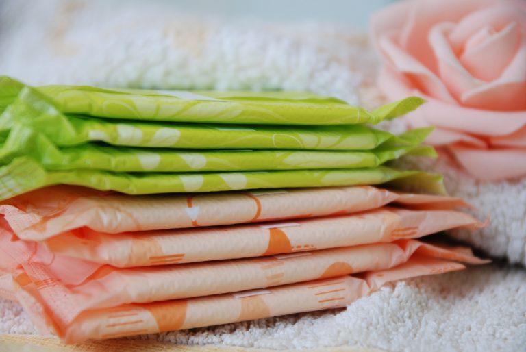 Pilha de absorventes com embalagens individuais verdes e rosas