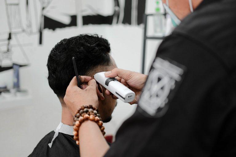 Imagem mostra uma pessoa usando um aparelho para aparar pelos da cabeça de um homem.