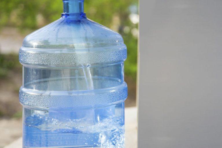 Imagem mostra um galão de água e com os canos da bomba passando por dentro.