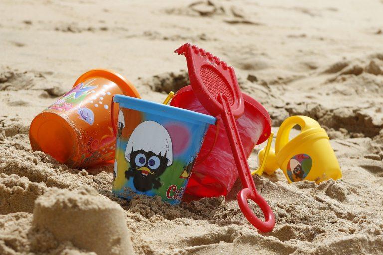 Imagem de brinquedos de praia coloridos de plástico na areia
