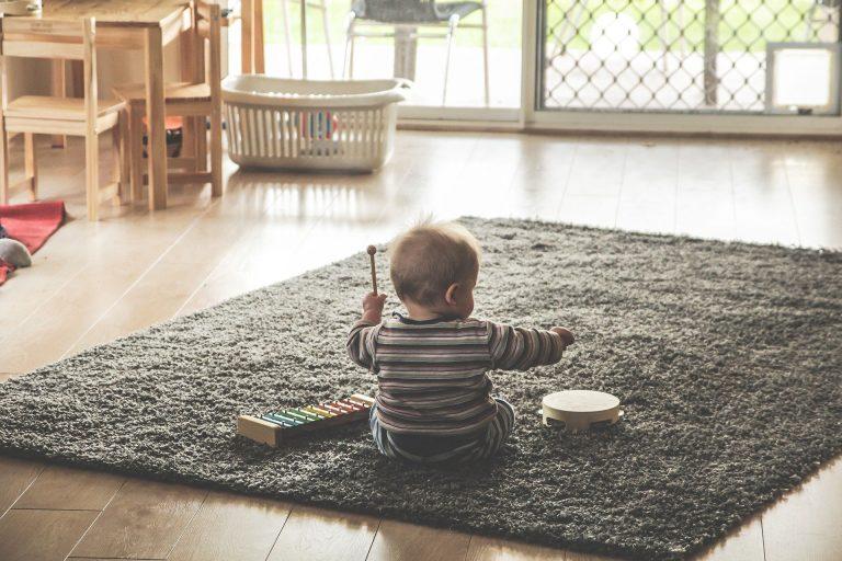 Na foto um bebê de costas sentado em um tapete brincando com um pandeiro.