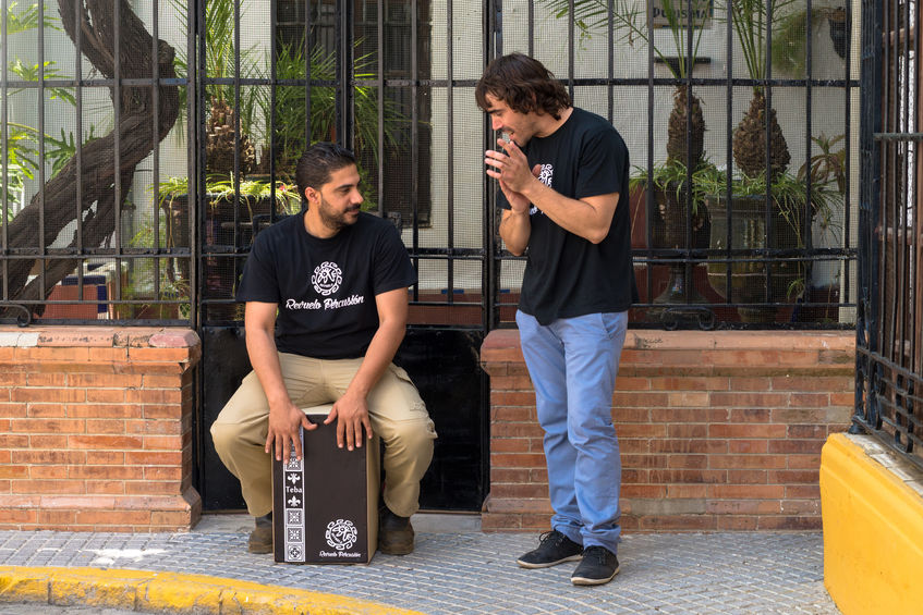 foto de dois homens na calçada, um sentado tocando cajon e o outro em pé batendo palma