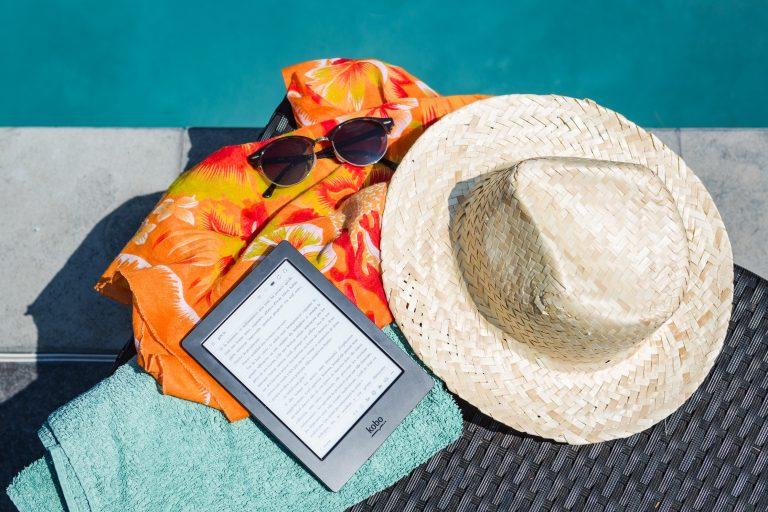 Na foto um chapéu panamá, um tablete, um óculos de sol, uma canga e uma tolha na frente de uma piscina.