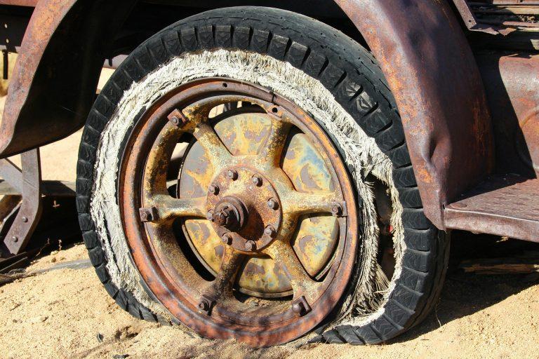 imagem de uma roda enferrujada e velha, presa a um veículo também em mau estado de conservação.