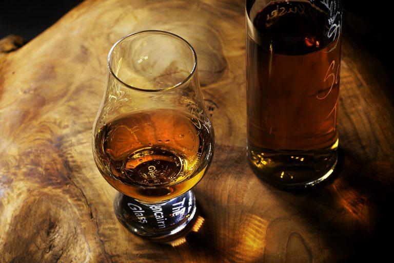 Imagem mostra um copo Glencairn ao lado de uma garrafa de whisky.