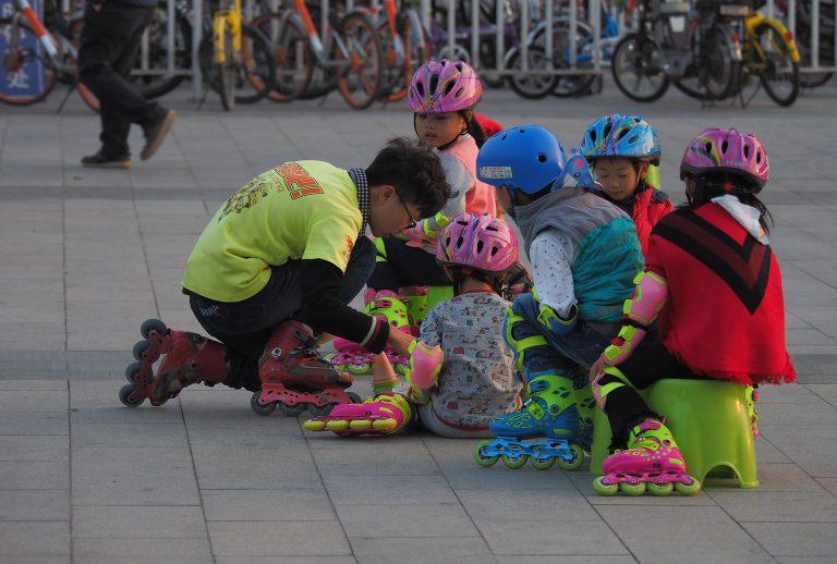 Grupo de crianças se prepara para patinar colocando equipamentos de segurança