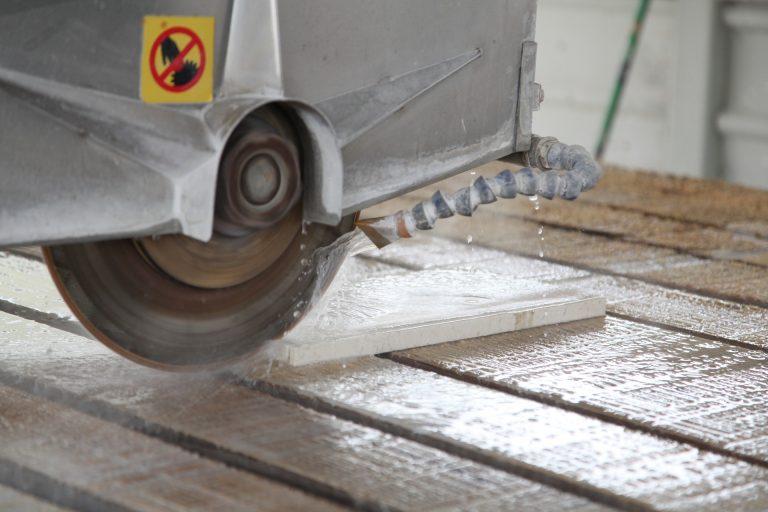 Imagem mostra um corte com disco sendo feito em um pedaço de mármore.