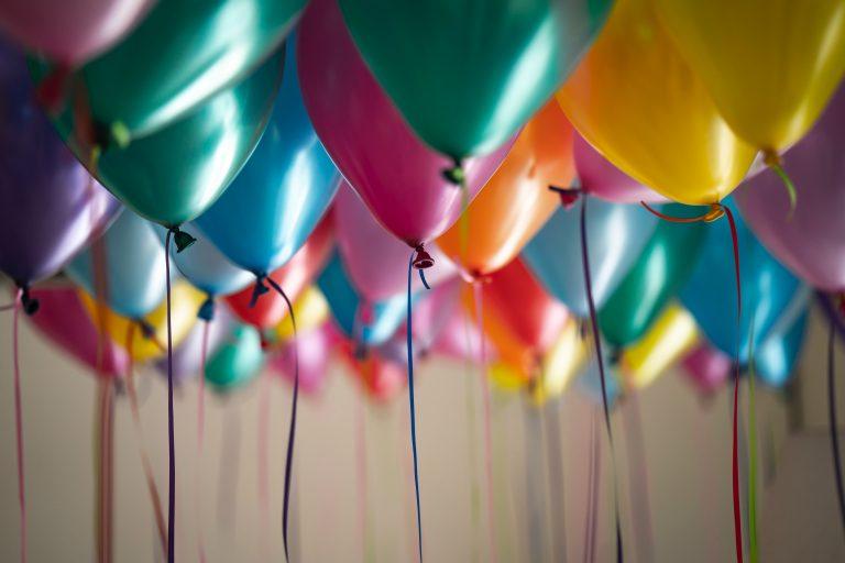 Imagem mostra um close de uma série de balões de festa e seus cordões amarrados em suas pontas.