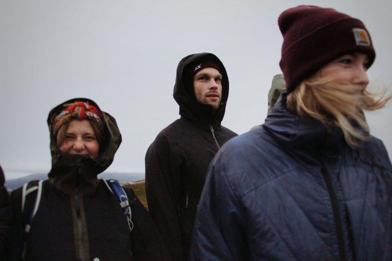 Imagem mostra três pessoas, duas mulheres e um homem, bem agasalhados, todos com jaquetas, no que parece ser o alto de um morro. Elas demonstram estar com frio.
