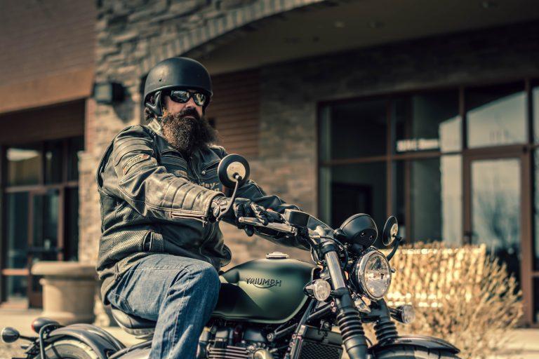 Imagem mostra um homem andando de motocicleta e usando uma jaqueta de motoqueiro.
