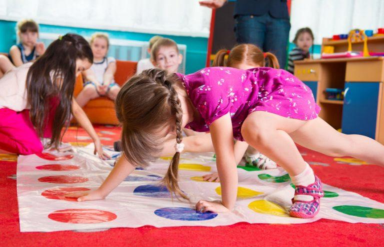 Imagem mostra um grupo de crianças jogando Twister numa sala de recreação.
