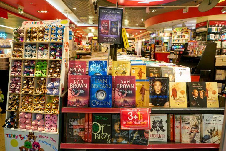 Imagem mostra uma livraria, com a sua primeira estante repleta de livros de autoria de Dan Brown. Ao fundo, um mar de livros e estantes, desfocados.