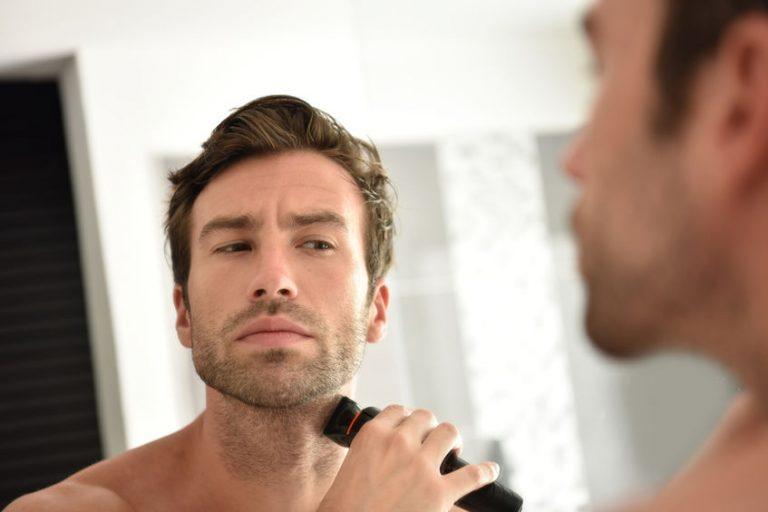 Imagem de homem de frente para o espelho se barbeando com uma máquina de barbear