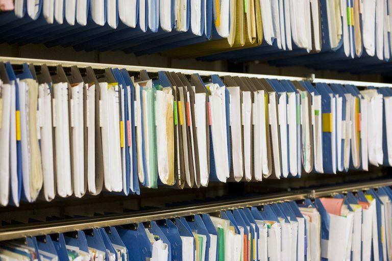 Imagem de várias pastas sanfonadas organizadas em estantes